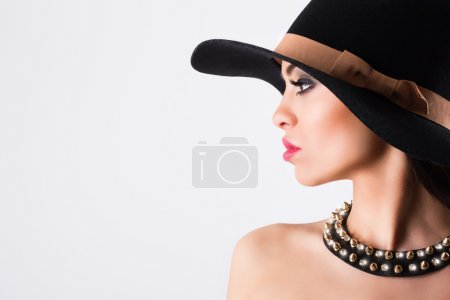 Elegant woman wearing black hat and necklace