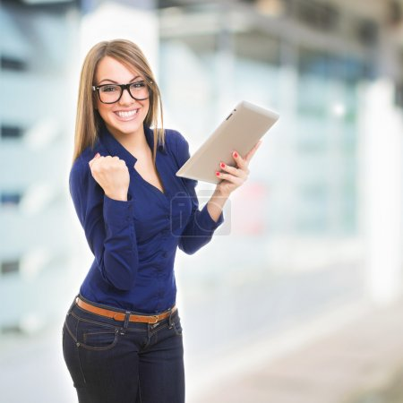 Photo for Happy young Caucasian businesswoman with eyeglasses holding tablet computer celebrating winning over blurred office building background. Copy-space available. - Royalty Free Image