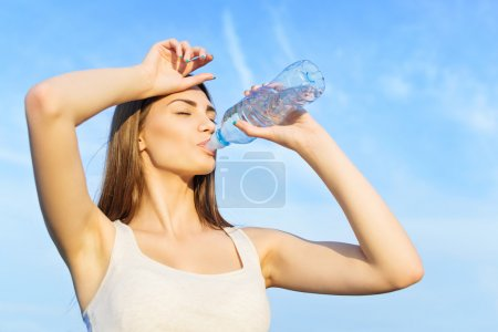 Cute young woman drinking water after workout
