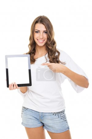 Attractive casual young woman showing tablet computer pointing at it