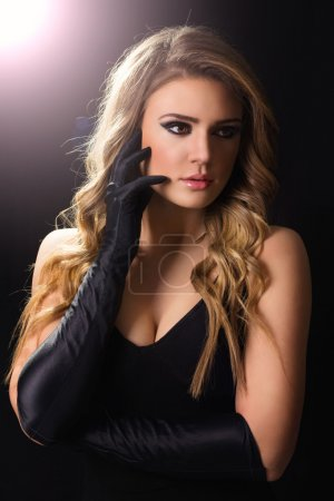 Glamorous young blonde woman in black