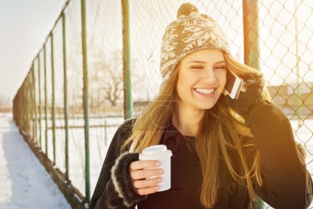 Happy young woman talking on the phone laughing