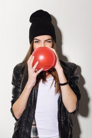 Photo pour Fille mignonne attrayant caucasien teenage hipster soufflant un ballon rouge portant en cuir veste et bonnet chapeau. - image libre de droit
