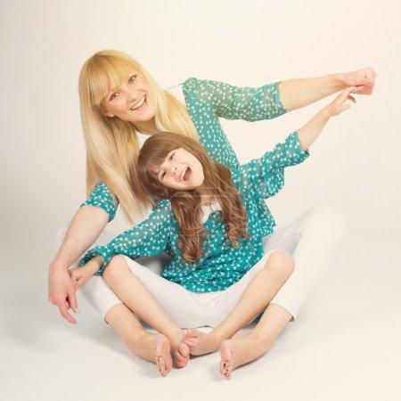 Photo pour Heureuse jeune maman blonde et brune fille 5 ans étreindre et souriant, portant correspondant à vêtements et tenant par la main comme ils volent. format d'image carrée avec retro filtre instantané appliquée. - image libre de droit