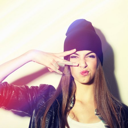Photo for Closeup studio shot of pretty hipster teenage girl with beanie hat pouting gesturing peace. Square image with instant filter applied. - Royalty Free Image