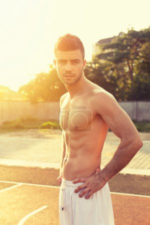 Fit shirtless young man outdoors on sunny summer day