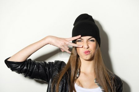 Photo for Hipster Caucasian teenage girl with black beanie hat posing making facial expression. Modern trendy young woman with attitude posing showing two fingers against white wall background. - Royalty Free Image