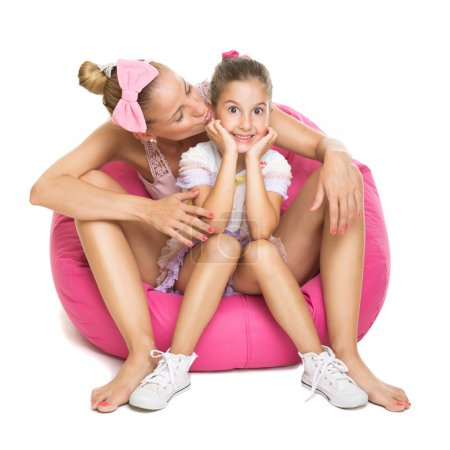 Photo for Closeup of pretty young mother and daughter sitting on pink bean bag. Mother kissing her daughter on cheek isolated on white background. - Royalty Free Image