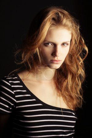 Photo for Portrait of a fashionable ginger model in t-shirt with black and white stripes over black background. studio shot - Royalty Free Image