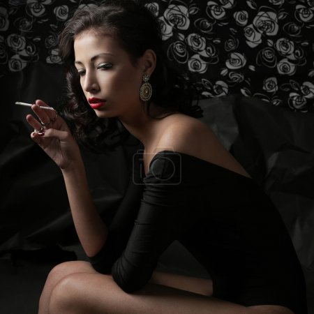 Smoking fashion brunette over a wrinkled black paper background.