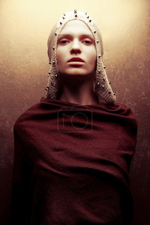 Photo for Art-fashion portrait of a glamorous queen-warrior in golden cape with golden pricks. Studio shot - Royalty Free Image