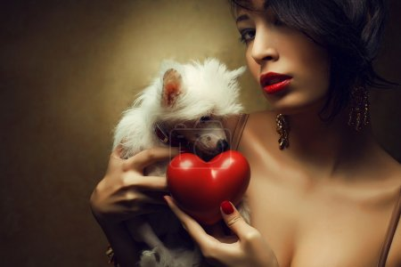 Portrait of two friends: fashionable model with sexy red lips holding red heart (love symbol) and white little chinese crested dog. Both posing over golden background. Profile. Close up. Copy-space