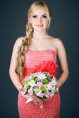 Portrait of a gorgeous long-haired blonde bridesmaid holding a w