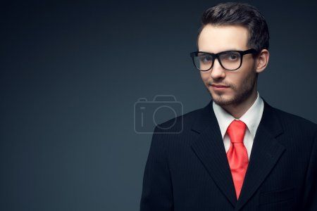 Portrait of a young handsome man (businessman) in black suit wit