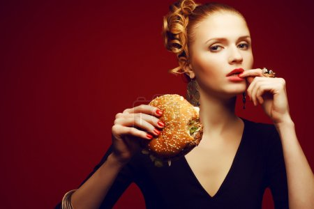 Photo for Unhealthy eating. Junk food concept. Portrait of fashionable young woman holding burger and posing over red background. Copy-space. Perfect hair, skin, make-up and manicure. Studio shot - Royalty Free Image