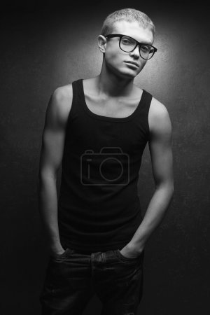 Photo pour Portrait of a casual young man wearing trendy glasses and posing over gray background with hands in jeans pockets. Hipster style. Black and white (monochrome) studio shot - image libre de droit