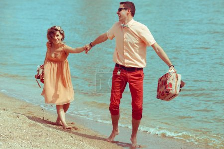 Couple walking on beach. Young happy married hipsters in trendy
