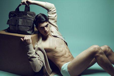 Male high fashion concept. Portrait of a handsome male model sit