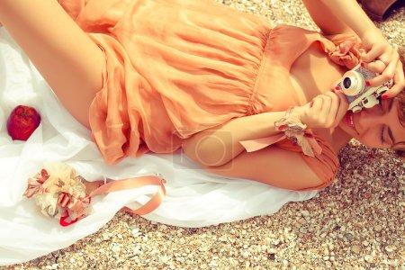 Photo pour Notion de pique-nique de l'été. Portrait d'une jeune femme heureuse se trouvant en bord de mer en robe trendy, tenant photocamera vintage et tir quelque chose. temps ensoleillé. coup de feu en plein air - image libre de droit