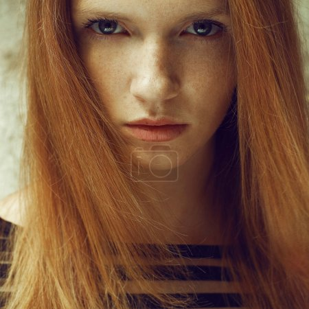 Emotive portrait of a fashionable model with red (ginger) hair a