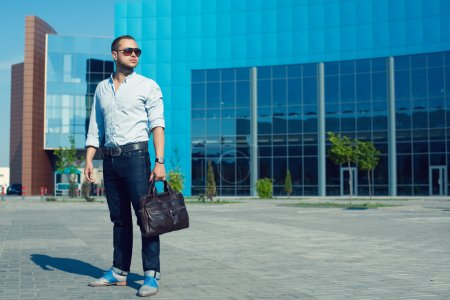 Photo for Hipster Man Concept. Portrait of attractive guy in trendy casual clothing with leather bag and sunglasses posing over shopping mall. Sunny summer weather with blue sky. Outdoor shot - Royalty Free Image