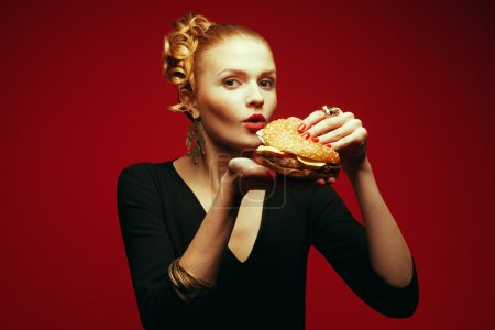 Fashion & Gluttony Concept. Portrait of luxurious red-haired model eating burger