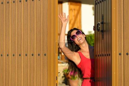 Happy woman opening door and welcoming