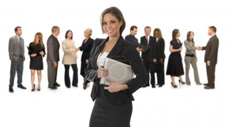 Photo pour Jeune, jolie femme professionnelle debout devant un fond blanc tenant un ordinateur portable - image libre de droit