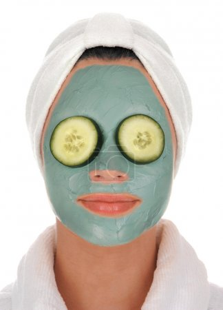 Photo pour Vue de face d'une belle jeune femme en peignoir éponge blanche et turban avec traitement facial masque boue de la mer profonde et concombres sur les yeux sur fond blanc - image libre de droit