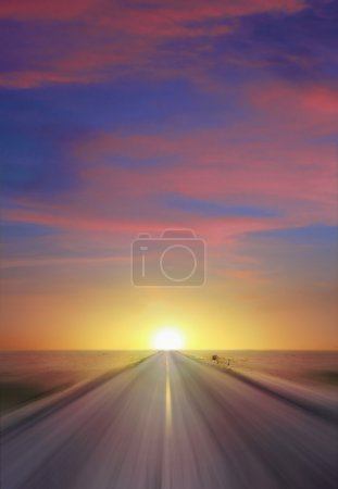 Photo for Sun setting at thte end of a straight two lane highway cutting through a flat expanse of desert wasteland and vanishing to a point on the horizon - Royalty Free Image