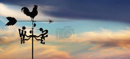 weathervane against cloudscape