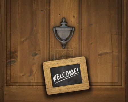 Photo pour Petit tableau noir accroché sur une porte sous le heurtoir de porte avec le mot « Bienvenue », écrit à la craie blanche - image libre de droit