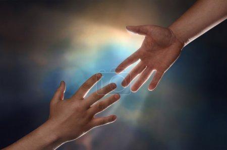 Photo pour Deux mains masculines, l'une tendue vers le bas pour aider une autre main tendue vers le haut avec un coup de soleil en arrière-plan - image libre de droit