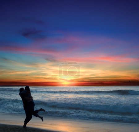 Photo for Couple embracing on the beach with a Pacific sunset in the background - Royalty Free Image