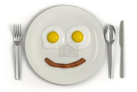 Photo pour Une assiette avec un visage fronçant les sourcils fait de deux œufs ensoleillés et une bande de bacon sur un fond blanc - image libre de droit