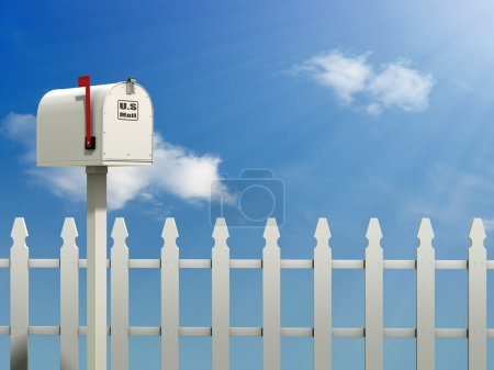 A Mail Box against a Blue Sky and white picket fen...