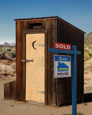 Photo pour Un signe de realestate montrant un out-house dumppy vendu dans le désert. - image libre de droit