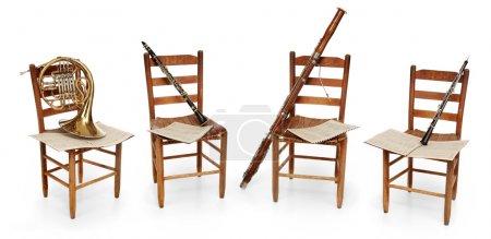 Photo pour Corne française, clarinette, basson et hautbois assis sur des chaises vides avec des partitions sur fond blanc - image libre de droit