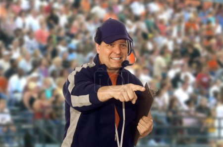 Photo for Coach wearing a headset on the field against a crowd - Royalty Free Image
