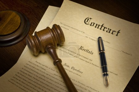 Contract on a wooden desk with a gavel and fountai...