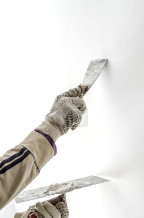 Closeup of a man aligning a wall with spatula and ...