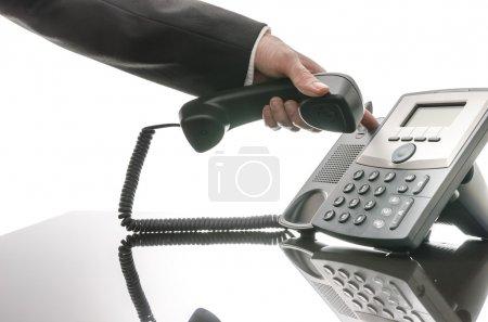 Foto de Vista recortada de un hombre de negocios a colgar el teléfono sobre una mesa negra. - Imagen libre de derechos