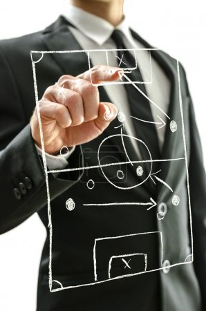 Photo for Man pointing at football field on a virtual screen to explain game strategy. - Royalty Free Image