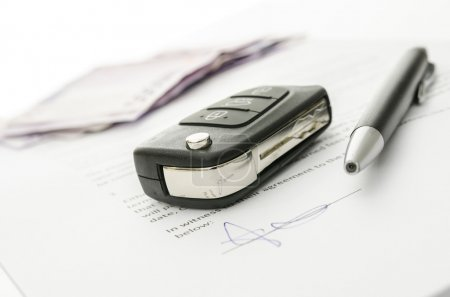 Car key on a contract of car sale