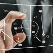Closeup of coach pointing to a football strategy p...