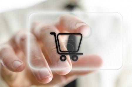 Photo pour Mâle han appuyant sur shopping panier sur écran virtuel. - image libre de droit