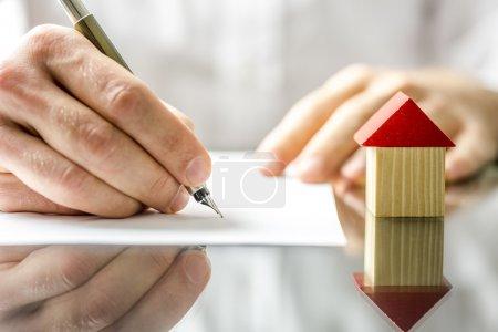 Photo pour Image conceptuelle d'un homme signant un prêt hypothécaire ou de contrat d'assurance ou de l'acte de vente lorsque vous achetez une nouvelle maison ou vendre son existant avec un petit modèle en bois d'une maison à côté - image libre de droit