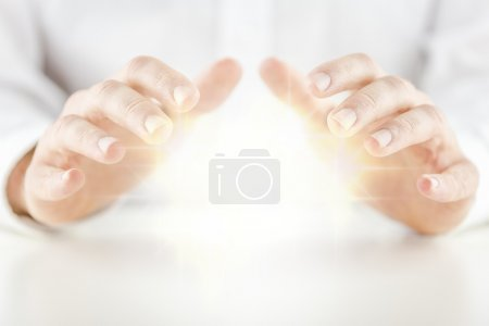 Photo for Man with a glowing crystal ball holding his hands protectively above it to feel the energy as he foretells or predicts the future conceptual of a fortune teller, soothsayer, mystic or clairvoyant - Royalty Free Image