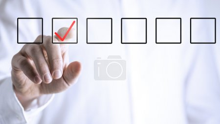 Photo for Man ticking a check box in a line of empty boxes on a virtual screen or interface with his finger - Royalty Free Image