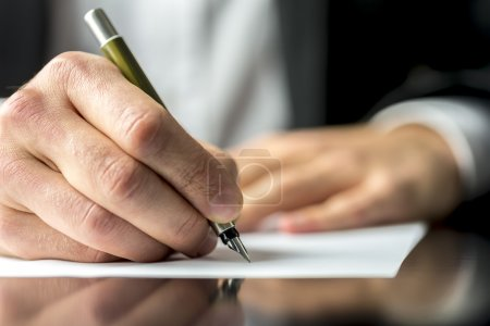 Photo for Close up of the hands of a businessman in a suit signing or writing a document on a sheet of white paper using a nibbed fountain pen - Royalty Free Image